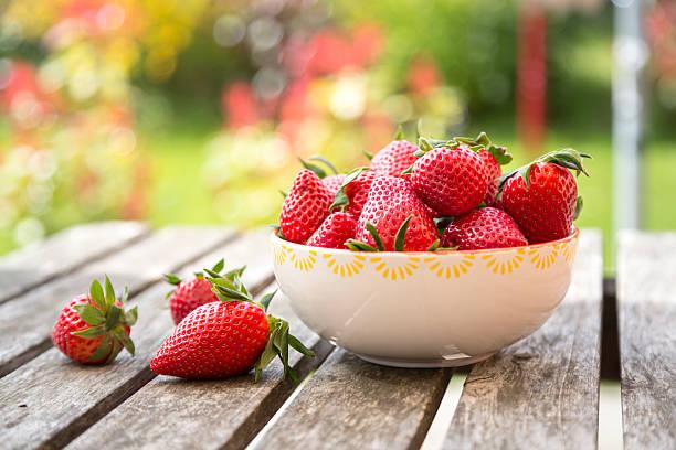 Bowl of strawberries on wooden garden table:スマホ壁紙(壁紙.com)