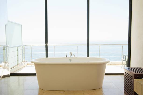 Modern bathroom with bathtub and large windows:スマホ壁紙(壁紙.com)