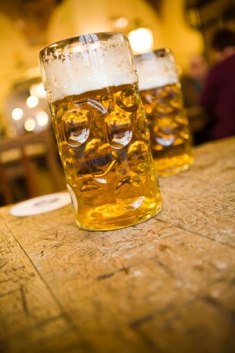 Oktoberfest「Two mugs of beer on a pub table.」:スマホ壁紙(15)