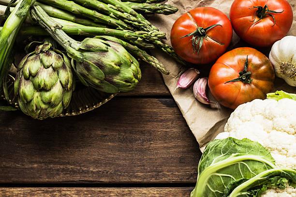 Cauliflower, artichokes, asparagus, garlic and tomatoes on wooden table:スマホ壁紙(壁紙.com)