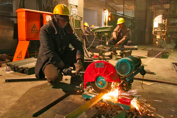 A Chinese worker cutting metal parts during the construction of air conditioning ducts in a new office town in central Beijing.:ニュース(壁紙.com)