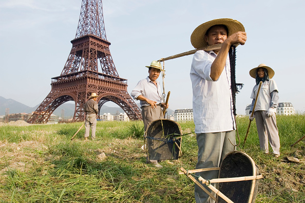 subUrbia - Named Work「Chinese workers stand in front of the Eiffel tower replica at Tiandu Cheng, a Parisian-themed residential development under construction in Hangzhou, China, August 11, 2007.  The development was designed by the Hangzhou Urban planning institute with cons」:写真・画像(15)[壁紙.com]
