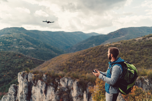 自然美「ビデオや写真をするドローンを飛んで山の頂上にハイカー」:スマホ壁紙(4)