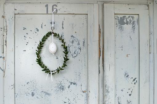 イースター「Easter egg and box tree wreath hanging in front of wooden door」:スマホ壁紙(12)