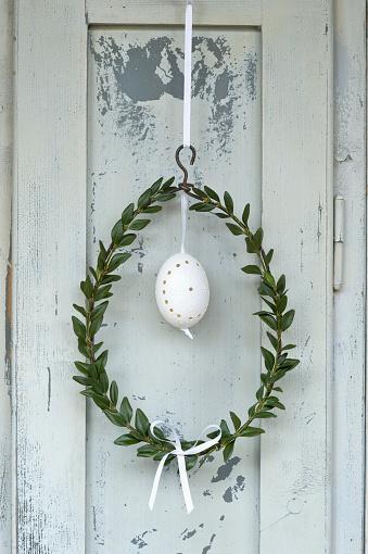 イースター「Easter egg and box tree wreath hanging in front of wooden door」:スマホ壁紙(11)