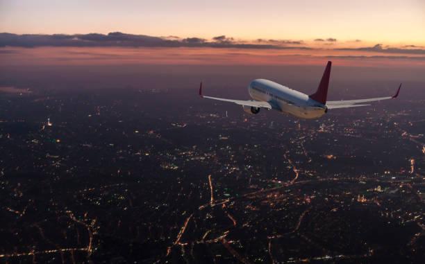 Commercial airplane flying over big city at dusk:スマホ壁紙(壁紙.com)