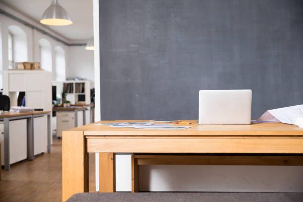 Laptop on desk in empty office:スマホ壁紙(壁紙.com)