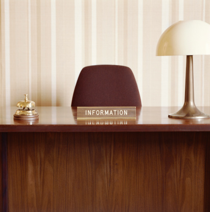 Hotel Reception「Empty desk with information sign, bell and lamp」:スマホ壁紙(5)
