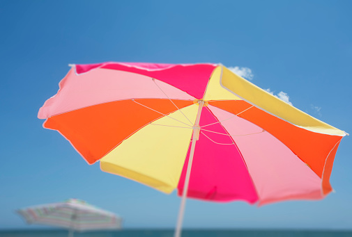 Sunshade「Colorful beach umbrella against blue sky」:スマホ壁紙(13)