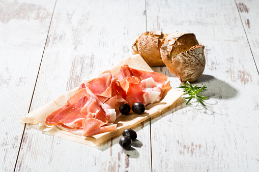 Parma Ham「Parma ham on greaseproof paper, rolls and black olives on bright wood」:スマホ壁紙(1)