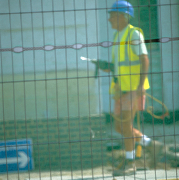 Defocused「Worker walking with drill seen through security fence」:写真・画像(19)[壁紙.com]