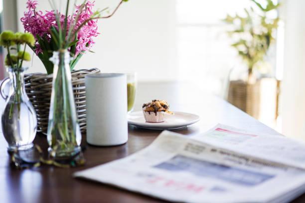 Newspaper, flower vases, loudspeaker and muffin on table:スマホ壁紙(壁紙.com)