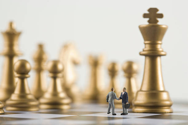 Two businessman figurines shaking hands a top chess board (focus on figurines):スマホ壁紙(壁紙.com)