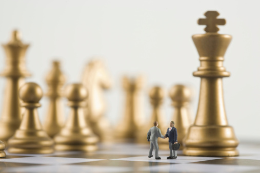 小さな像「Two businessman figurines shaking hands a top chess board (focus on figurines)」:スマホ壁紙(8)