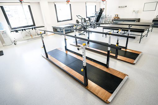 Occupational Therapy「View of a physical recovery clinic with parallel bars, machines, gurneys」:スマホ壁紙(8)