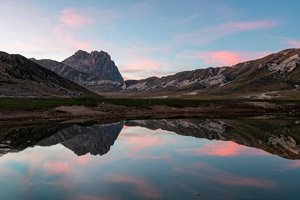 Italy, Abruzzo, Gran Sasso e Monti della Laga National Park, plateau Campo Imperatore, Corno Grande peak reflected in lake Petranzoni at sunset:スマホ壁紙(壁紙.com)
