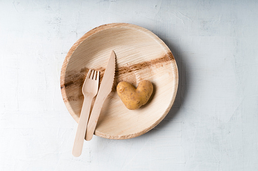 Silverware「Potato in heart shape and wooden fork and knife on palm leaf plate」:スマホ壁紙(9)