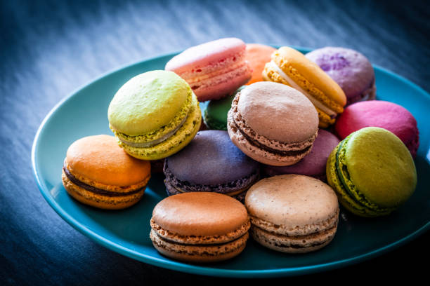 Multi colored macaroons in a blue plate shot on blue table:スマホ壁紙(壁紙.com)