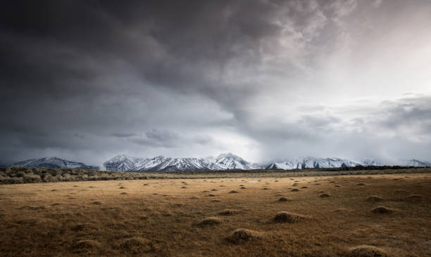 Open Field Shows Evidence of Geothermal Activity, Snow-capped Mountains in Distance, Stormy Sky:スマホ壁紙(壁紙.com)