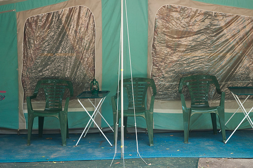 Camping Chair「Empty camping chairs in front of a tent in a caravan park along a river」:スマホ壁紙(5)