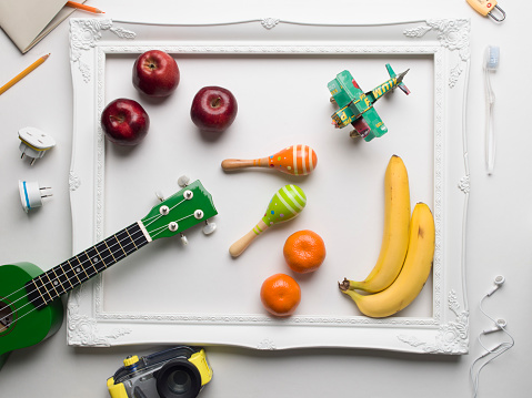 Guitar「Musical instruments, objects representing travel and colourful fruit displayed around a white picture frame on a white background」:スマホ壁紙(13)
