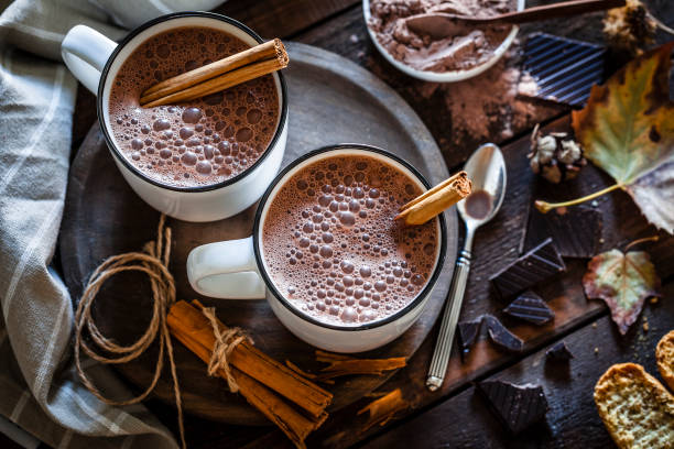 Two homemade hot chocolate mugs on rustic wooden table:スマホ壁紙(壁紙.com)