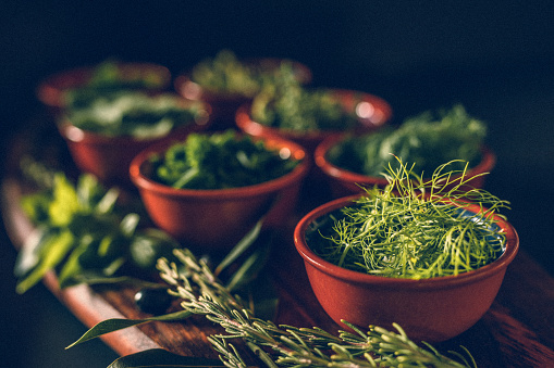 Fennel「Low key of different green herbs on a rustic wooden board with focus on the fennel」:スマホ壁紙(5)