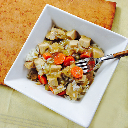 Basmati Rice「Chicken fricassee in a white bowl with a fork and napkin on a table with birdseye maple cutting board」:スマホ壁紙(7)