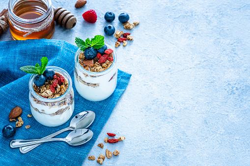 Yogurt Container「Healthy food: homemade yogurt and granola on blue table. Copy space」:スマホ壁紙(18)