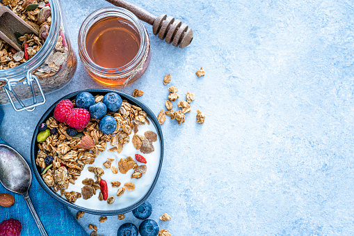 Bowl「Healthy food: homemade yogurt and granola shot from above on blue table. Copy space」:スマホ壁紙(12)