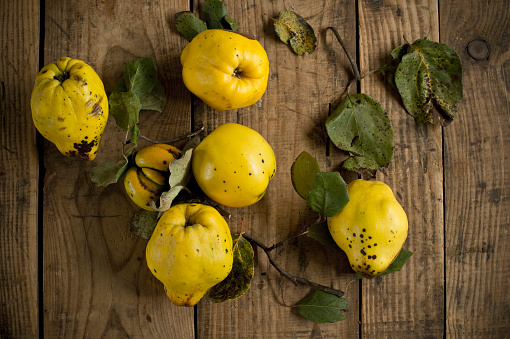 Quince「Fresh yellowquinces lying on wooden surface」:スマホ壁紙(15)