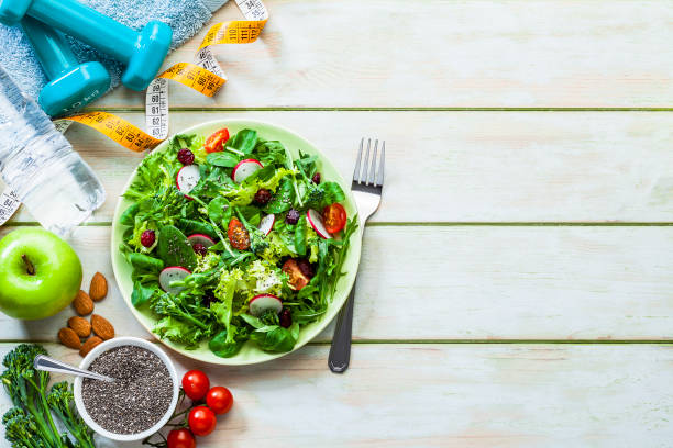Healthy eating and exercising backgrounds: Fresh healthy salad, dumbbells and tape measure with copy space:スマホ壁紙(壁紙.com)
