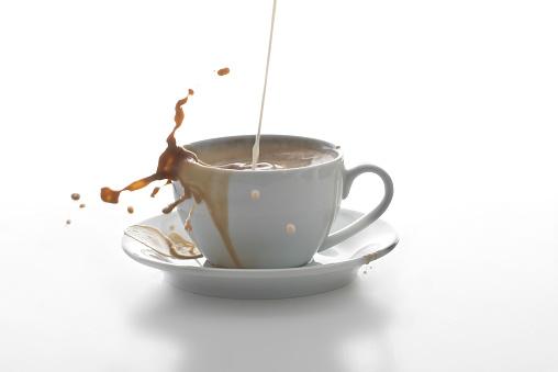 Splashing「Milk splashing in a cup of coffee in front of white background」:スマホ壁紙(12)