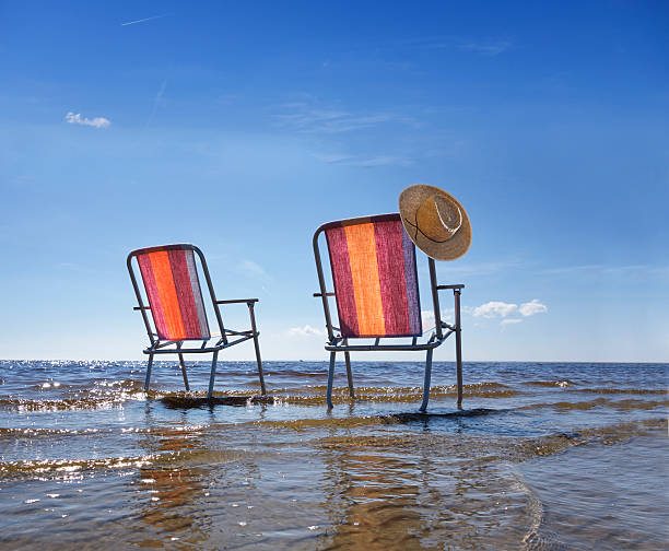 Estonia, two folding chairs standing in water at shore:スマホ壁紙(壁紙.com)