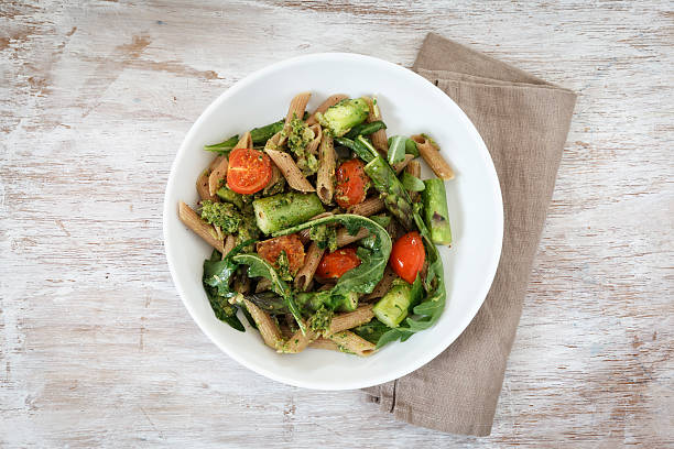 Wholemeal spelt rigatoni with green asparagus, cherry tomato and rocket pesto on plate:スマホ壁紙(壁紙.com)