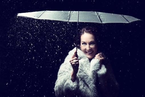 女性モデル「Beautiful woman with fur coat standing in rain under an umbrella at night - Studio, South Africa」:スマホ壁紙(12)