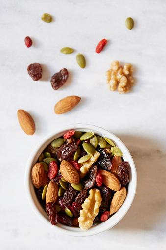 Walnut「Bowl of nuts and raisins on white background」:スマホ壁紙(11)