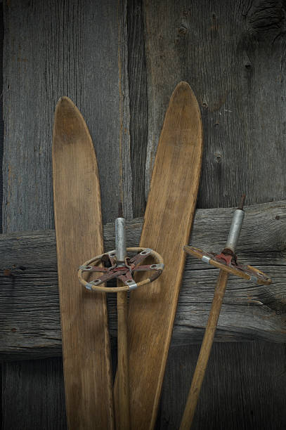 Old skis, and ski poles leaning on wooden wall:スマホ壁紙(壁紙.com)