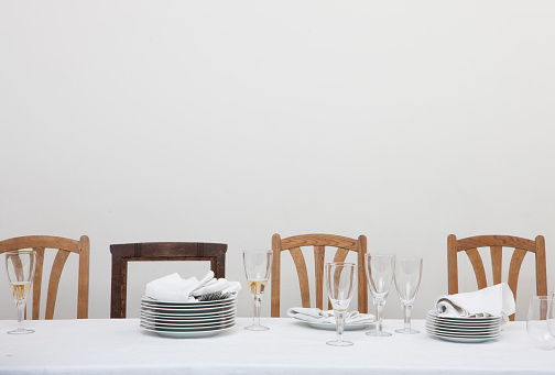 Place Setting「Table setting with empty wooden chairs, white table cloth and white plates, glasses of wine」:スマホ壁紙(11)