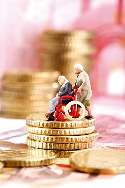 Figurines in wheelchair on pile of coins, side view:スマホ壁紙(壁紙.com)