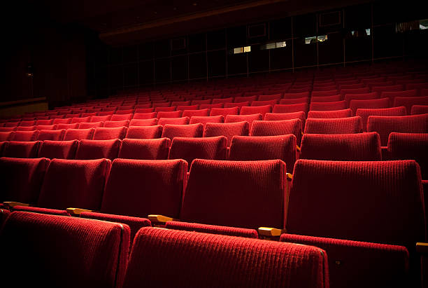 Empty theatre with red seats in low light:スマホ壁紙(壁紙.com)