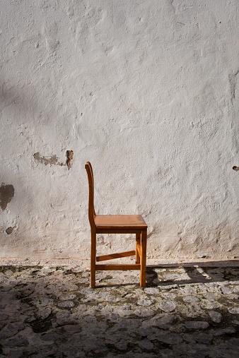 寂しさ「Profile of chair in front of white wall」:スマホ壁紙(13)