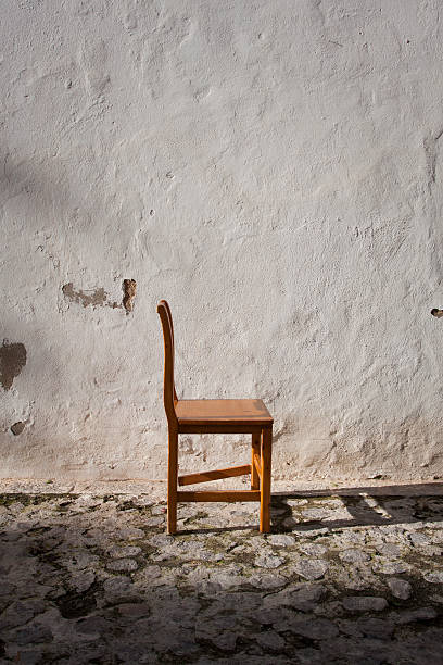 Profile of chair in front of white wall:スマホ壁紙(壁紙.com)