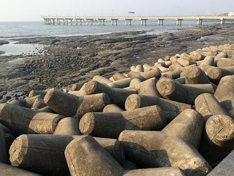 Groyne「India, Mumbai, Concrete tetrapods on beach and bridge on background」:スマホ壁紙(13)