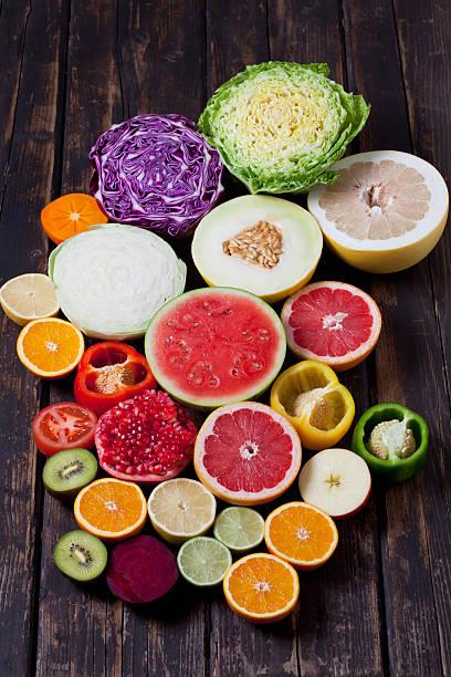 Halves of different vegetables and fruits on dark wood:スマホ壁紙(壁紙.com)