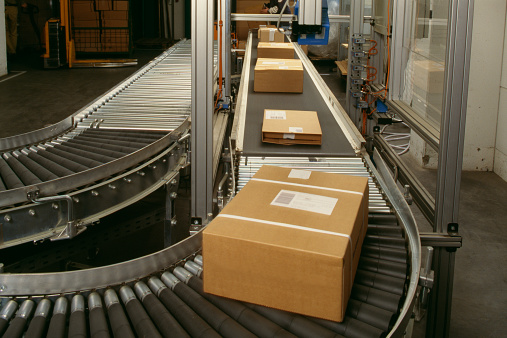 In A Row「Conveyor belt curve showing brown packed postal boxes」:スマホ壁紙(2)