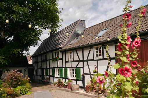 花「Exterior of a German haft timbered (Fachwerk) 18th century farmhouse with barn conversion and cottage garden」:スマホ壁紙(1)