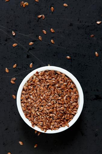 Flax Seed「Bowl full of flax seeds on black background」:スマホ壁紙(18)