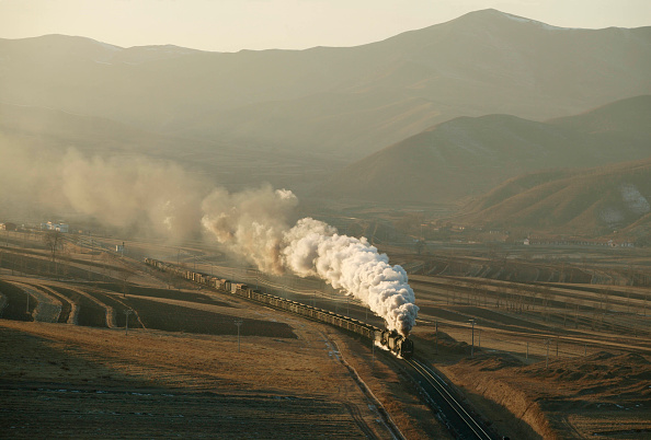 Extreme Terrain「Afternoon shadows lengthen as a pair of China Railways QJ Class 2-10-2s head a mixed freight towards Erdi and Brickworks Viaduct on the Jing Peng Pass section of the Ji-Tong in Inner Mongolia. This December 2004 scene depicts a village in the background.」:写真・画像(17)[壁紙.com]