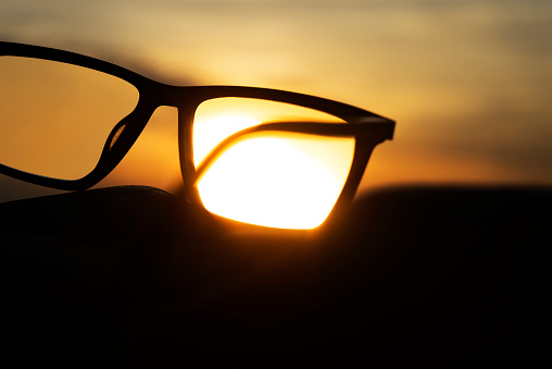 Eyesight「A series of abstract images of black rimmed reading glasses at sunset with selective focus」:スマホ壁紙(12)
